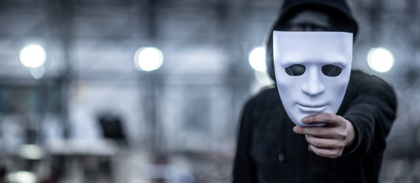 Mystery hoodie man with black mask holding white mask in his hand. Anonymous social masking or bipolar disorder concept. Mystery hoodie man with black mask holding white mask in his hand. Anonymous social masking or bipolar disorder concept. mask disguise stock pictures, royalty-free photos & images