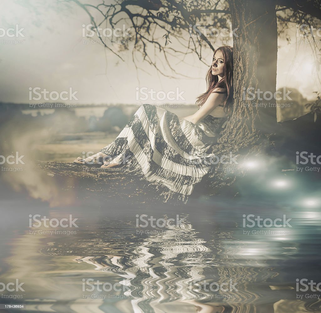 mystery lake view young woman sitting on a big tree at spring meadow Adult Stock Photo