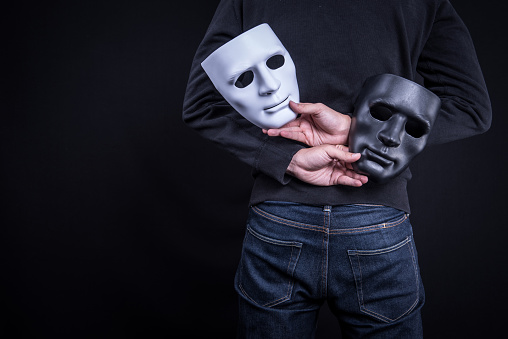 istock Mystery man holding black and white mask. Anonymous social masking concept. 827814702