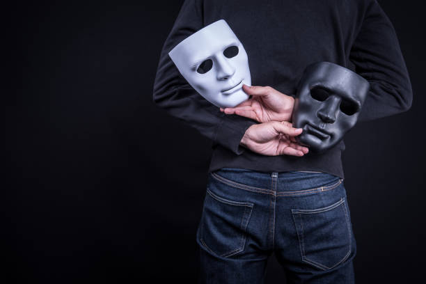 mystery man holding black and white mask. anonymous social masking concept. - imitation stock photos and pictures