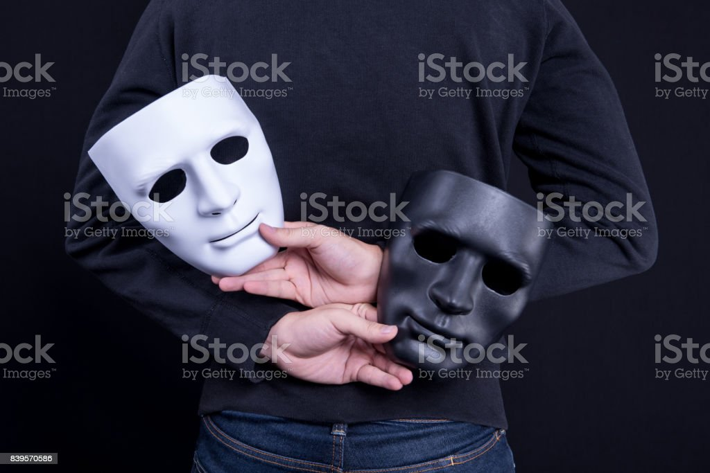 Mystery man holding black and white mask. Anonymous social masking concept. stock photo