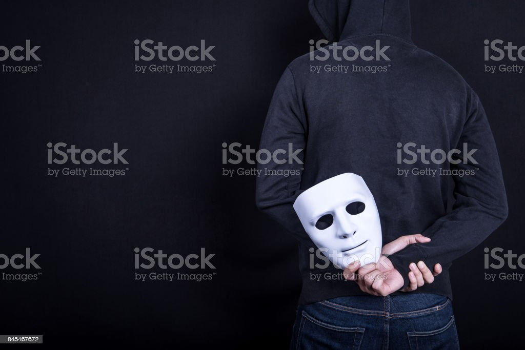 Mystery man holding white mask in the back stock photo