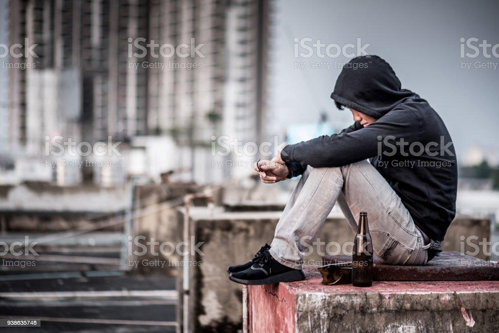Misterio del hombre sentado y abraza sus rodillas para arriba con una botella vacía y rota en edificio abandonado - Foto de stock de Suicidio libre de derechos