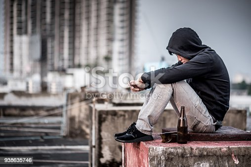 istock Mystery man sitting and hugs his knees up with an empty and broken bottle in abandoned building 938635746