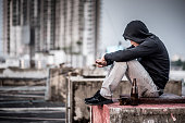 Mystery man in hoody jacket, sitting and hugs his knees up with an empty and broken bottle in abandoned building. depression self destruction suicidal addicts drug, Major depressive disorder concept