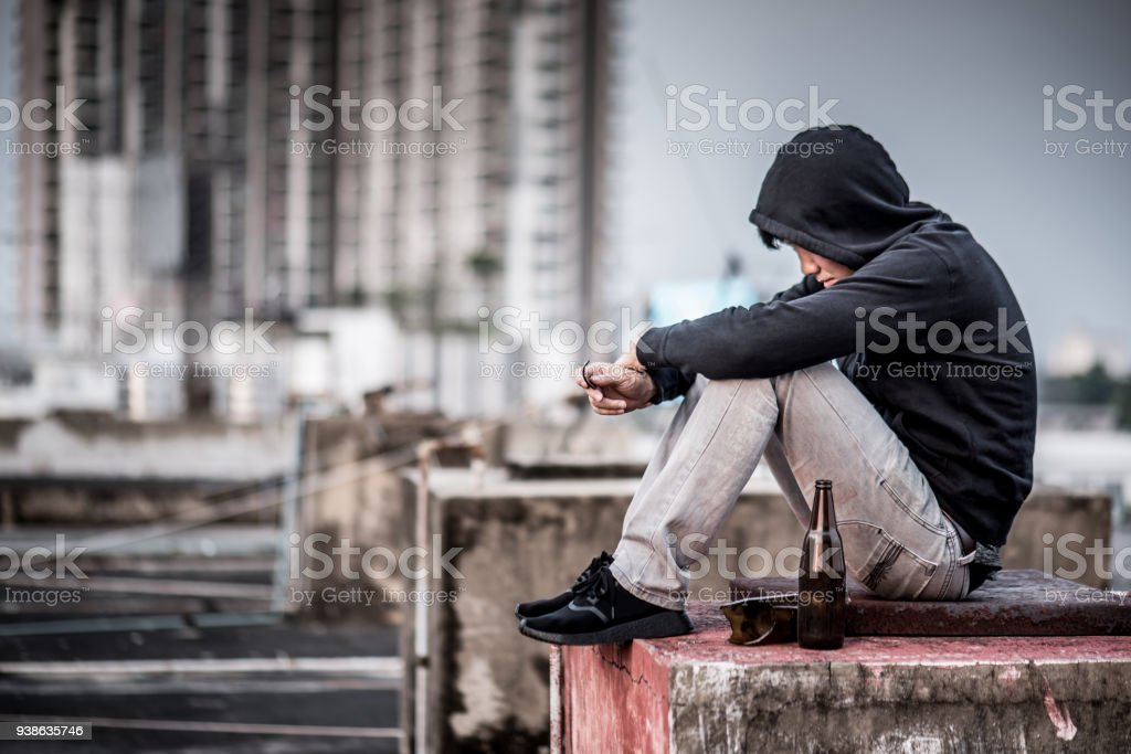 Mystery man sitting and hugs his knees up with an empty and broken bottle in abandoned building stock photo