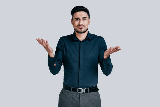 Mystery! Confused young man shrugging shoulders and making face while standing against grey background shrugging stock pictures, royalty-free photos & images