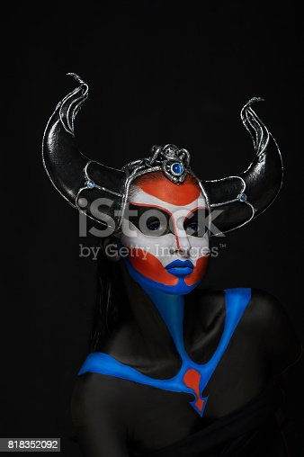 860524946 istock photo Mystery portrait of female faun with blue eyes, body art and silver snakes on black horns 818352092