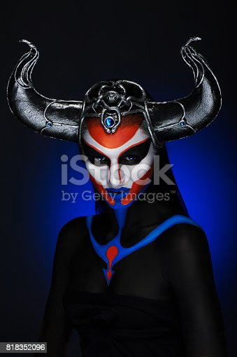 860524946 istock photo Mystery portrait of female faun with blue eyes, body art and silver snakes on black horns 818352096