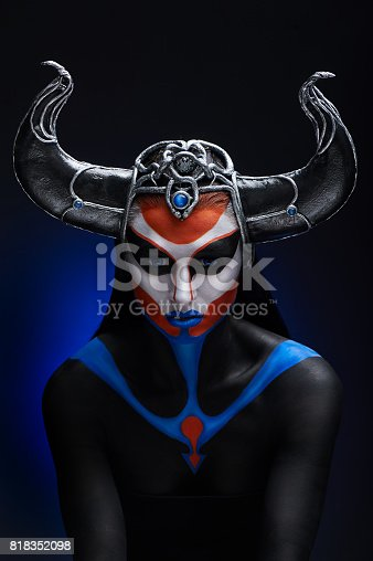860524946 istock photo Mystery portrait of female faun with blue eyes, body art and silver snakes on black horns 818352098