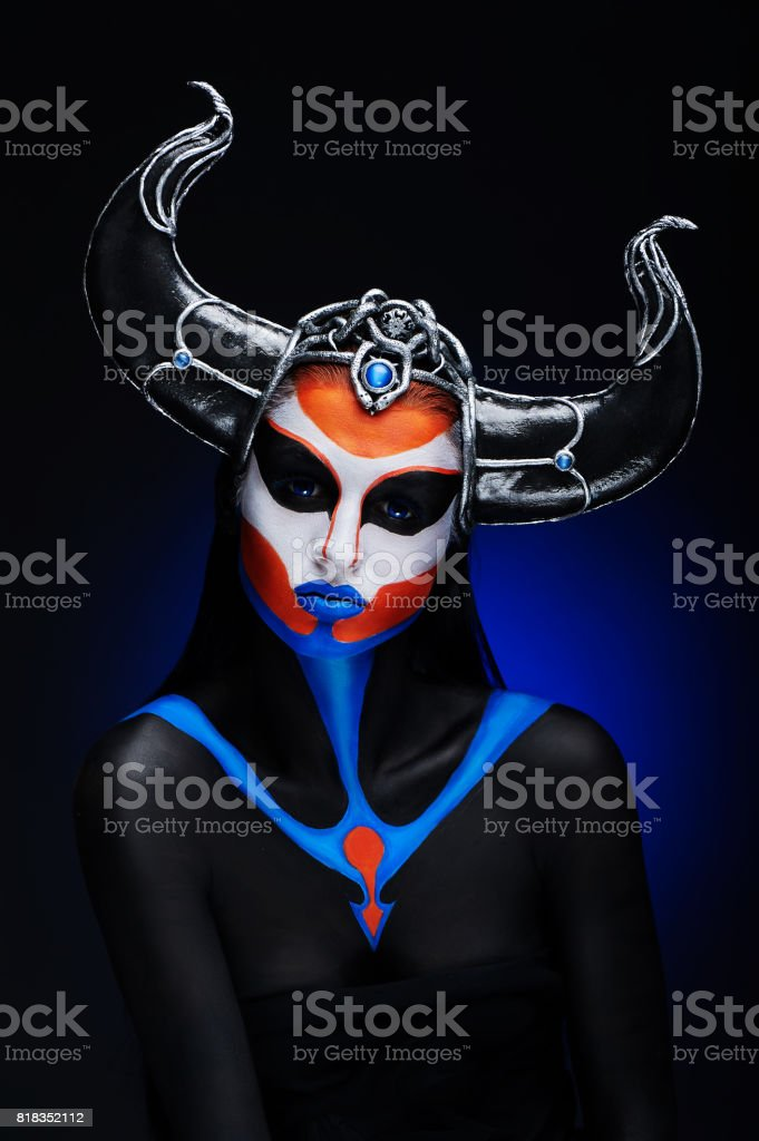 Mystery portrait of female faun with blue eyes, body art and silver snakes on black horns stock photo