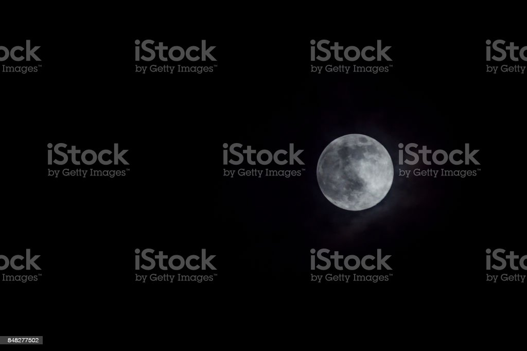 Mystic full moon in night sky with clouds.