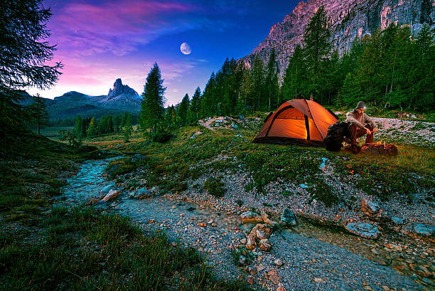 mystical night landscape, in the foreground hike, campfire and tent - camping stock photos and pictures