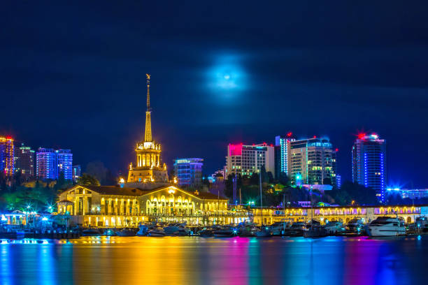 Mystical Sochi, Central Marine Station, Welcome to Russia 2018. The building of the city seaport against the background of high-rise buildings at night, with the moonlight hidden behind the clouds. sochi stock pictures, royalty-free photos & images