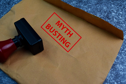Myth Busting text on document above brown isolated on Office Desk