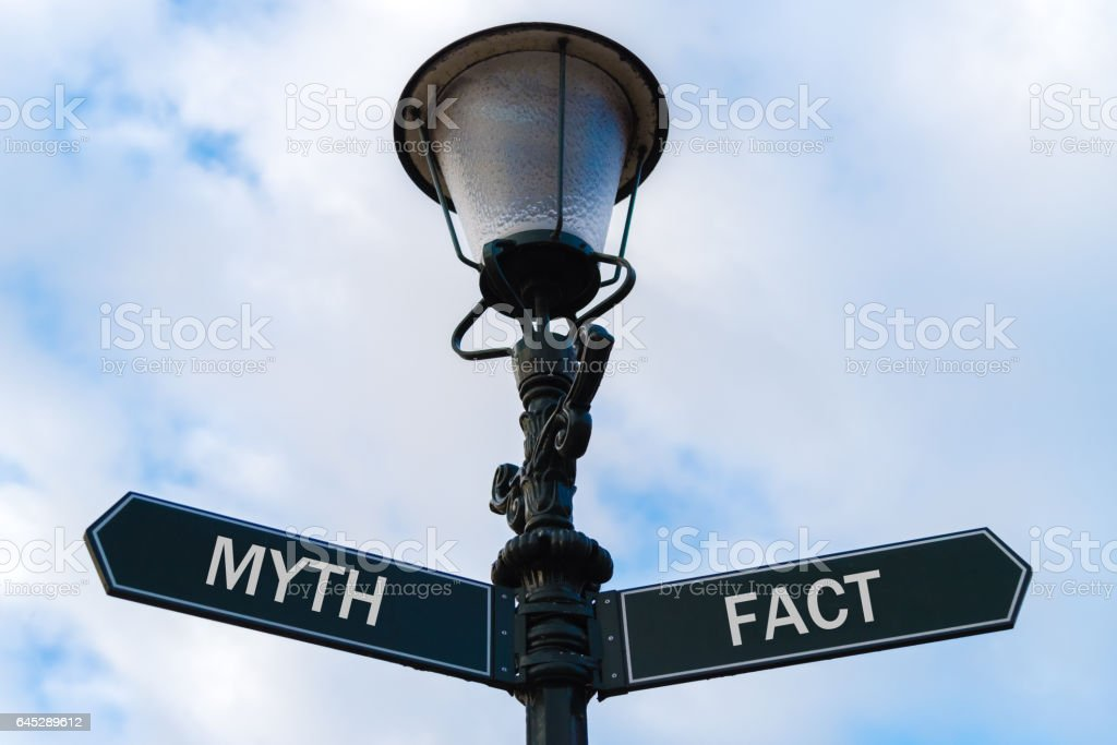 Myth versus Fact directional signs on guidepost stock photo