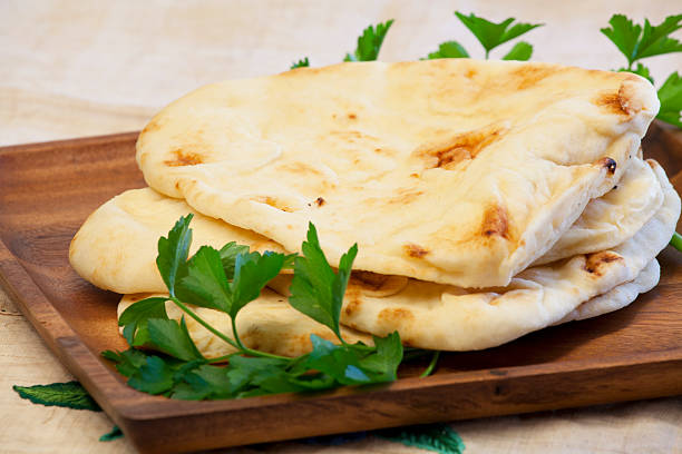 Naan Bread on Wood Platter Delicious fresh naan bread garnished with parsley on a wood platter rests on a rustic embroidered linen cloth.Naan a flatbread which is a staple in South and Central Asia and is traditionally cooked in a clay oven.  The flatbread may have originated from Iran. naan bread stock pictures, royalty-free photos & images