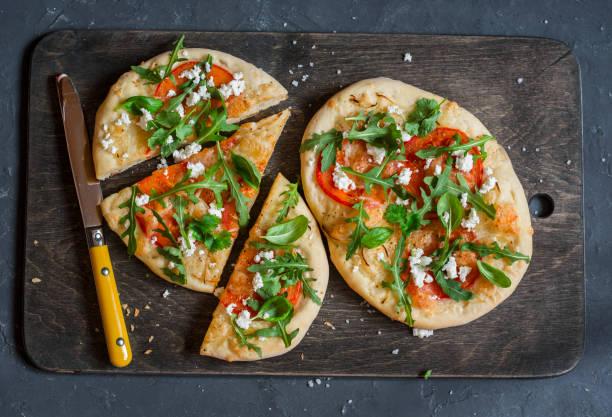 naan pizza on a dark wooden background, top view - fladenbrotpizza stock-fotos und bilder
