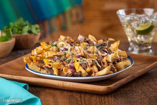 a plate of nacho fries and tequila