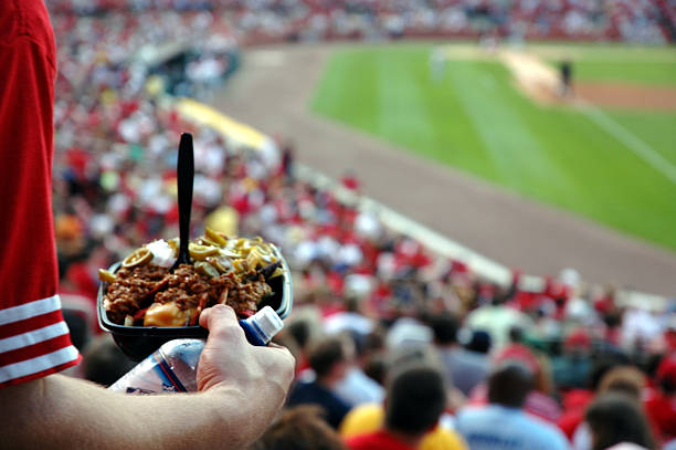 Nachos & Sports A man makes his way back to his seat with a fist full of nachos. baseball sport stock pictures, royalty-free photos & images