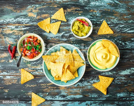 Mexican tortilla chips with guacamole, cheese, salsa dips. Nachos and assorted dips. Mexican party food, appetizers. Top view. Tortilla chips, sauces, hot pepper, avocado, rustic wooden background