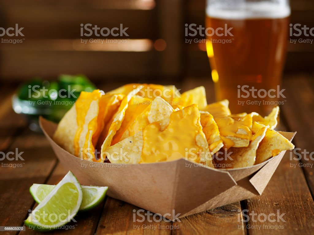 nachos and cheese in tray with beer stock photo