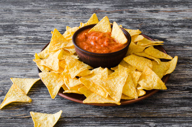 Nachos corn chips with spicy tomato sauce. Nachos corn chips with spicy tomato sauce. Mexican food concept. Yellow corn totopos chips with salsa sauce. Top view. salsa sauce stock pictures, royalty-free photos & images