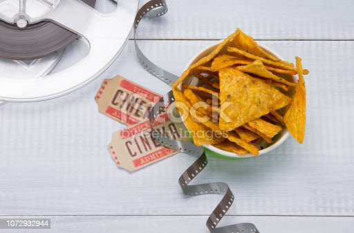 nachos in a bucket, two tickets for movies and film, on a light gray background, close-up