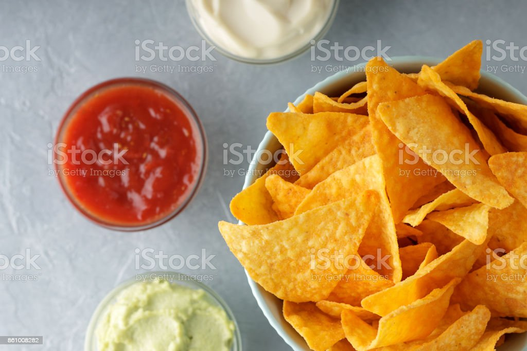 Nachos or tortilla in bowl with dipping sauces on gray background. stock photo