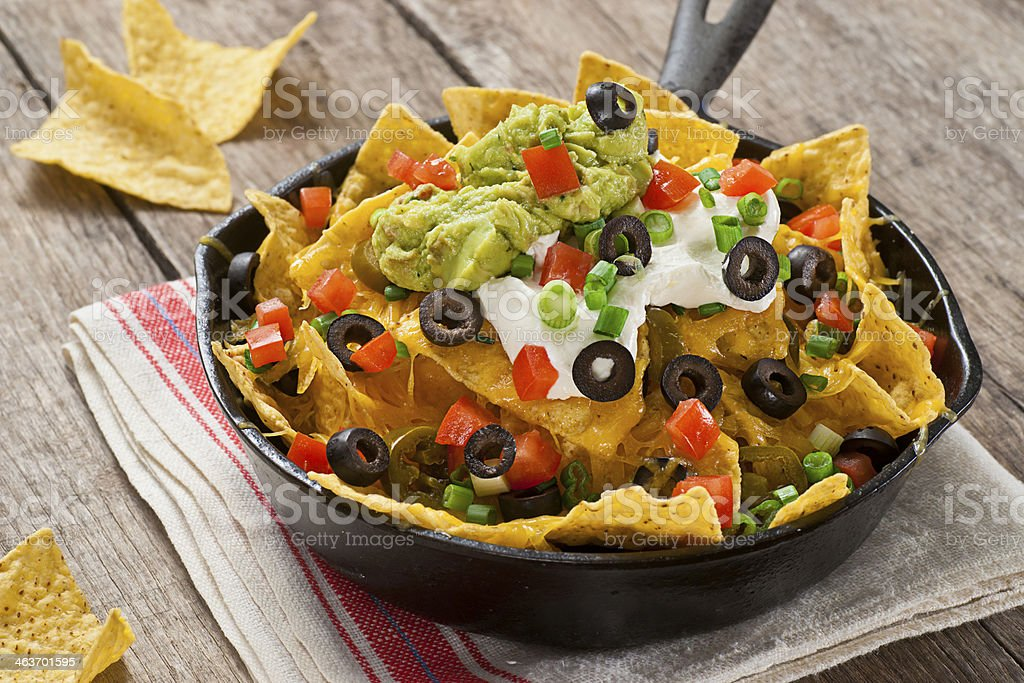 Nachos Nachos with cheddar cheese, green onions, jalapenos, tomatoes, black olives, guacamole, and sour cream. Appetizer Stock Photo