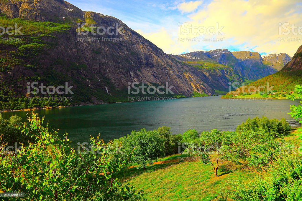 Naeroyfjord: fjord mountains and green farm at sunset, Norway stock photo