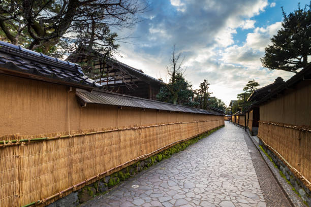 Nagamashi district or samurai district street over a dramatic sky showing the earthen walls, tsuchi-kabe, covered in winter with straw mats, Ishikawa prefecture, Japan. stock photo