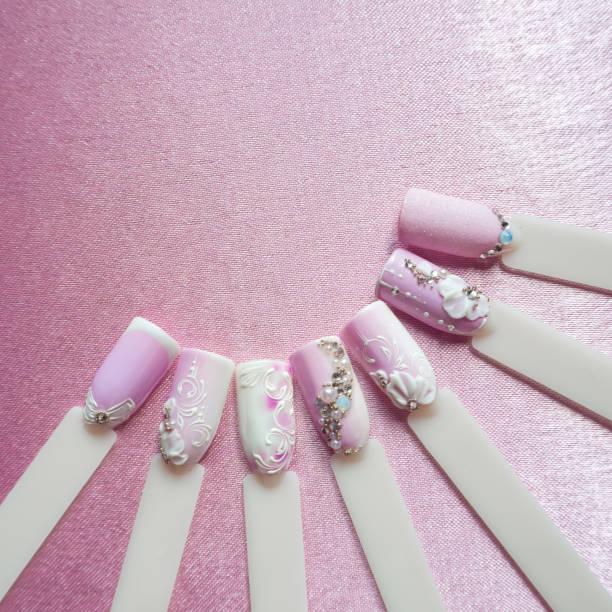 Nail art création avec strass sur fond rose. - Photo