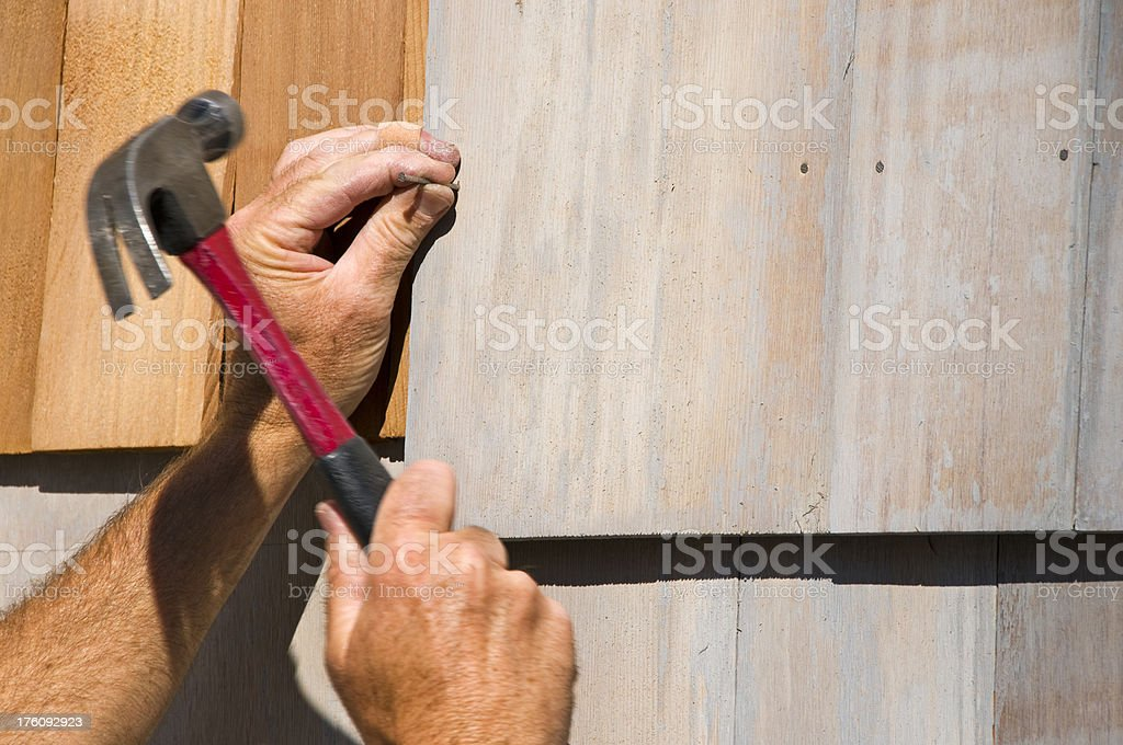 Nail being hammered into cedar shingle stock photo