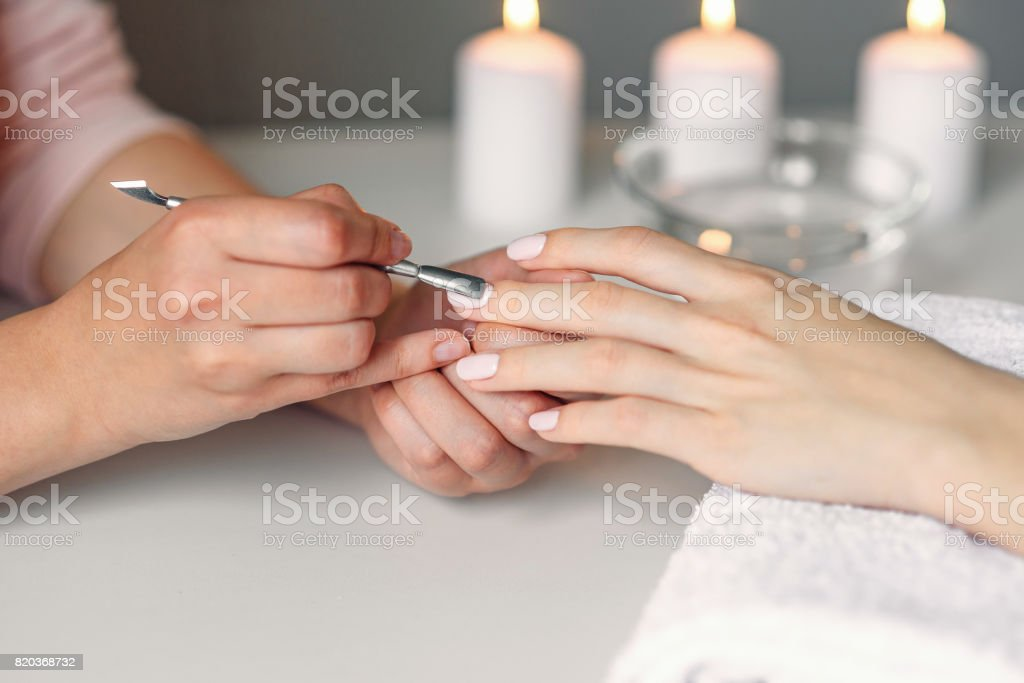 Nail care. Closeup of beautiful woman hands getting manicure in spa salon. Female manicurist cleaning cuticle with professional manicure pusher tool. Cosmetic procedure. stock photo