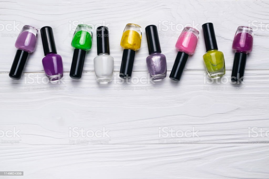 Nail polish bottles in different colors on white wooden background...