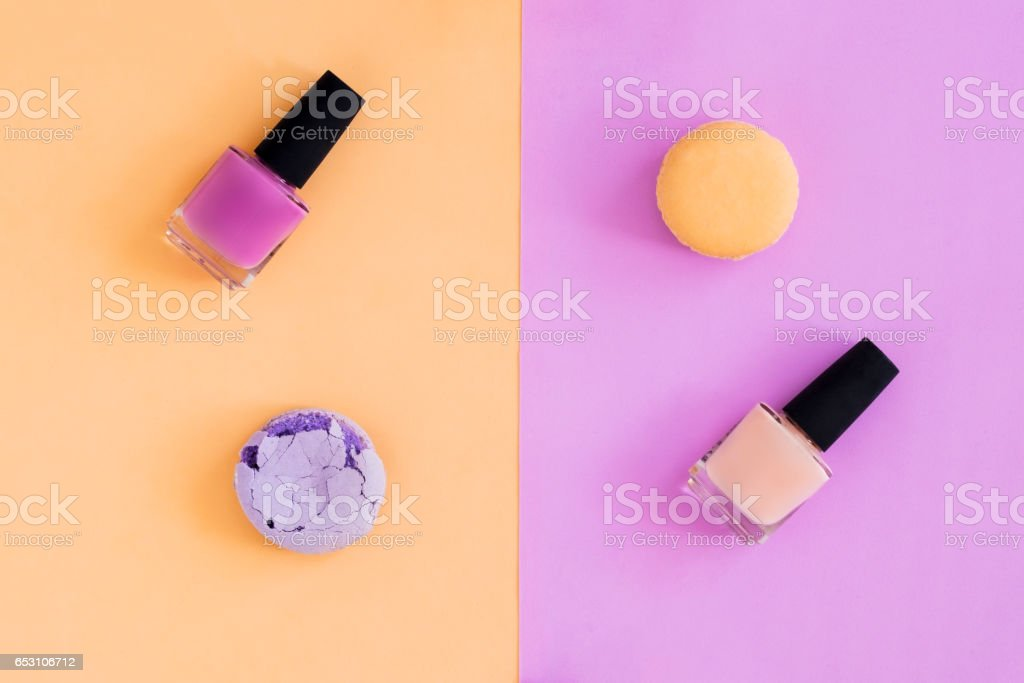 Nail polishes and macaroons on colorful background stock photo