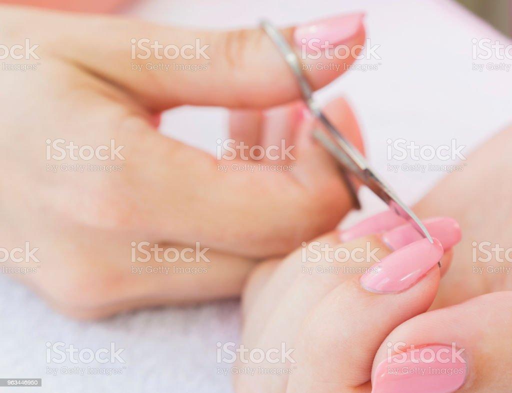 Nożyczki do paznokci w dłoni kobiety. Zbliżenie, selektywne skupienie. - Zbiór zdjęć royalty-free (Ciało ludzkie)