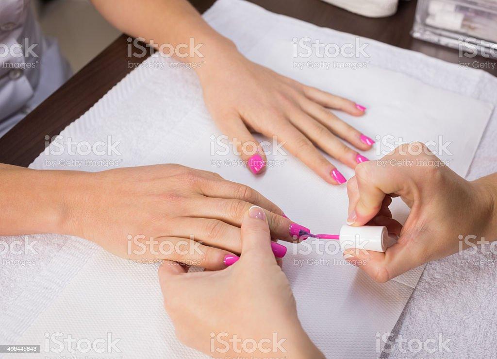 Nail technician applying pink nail varnish to finger nails at the...