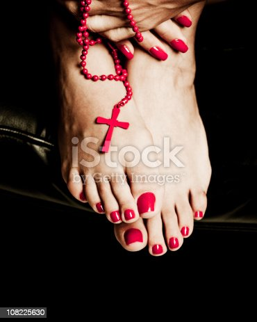 details of a woman hand and feet with nails done with a red crucifix