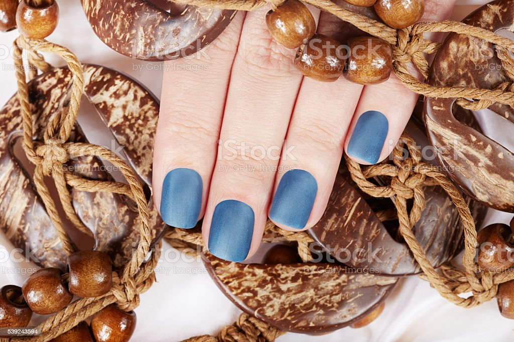 Nails with matte manicure and wooden necklace royalty-free stock photo
