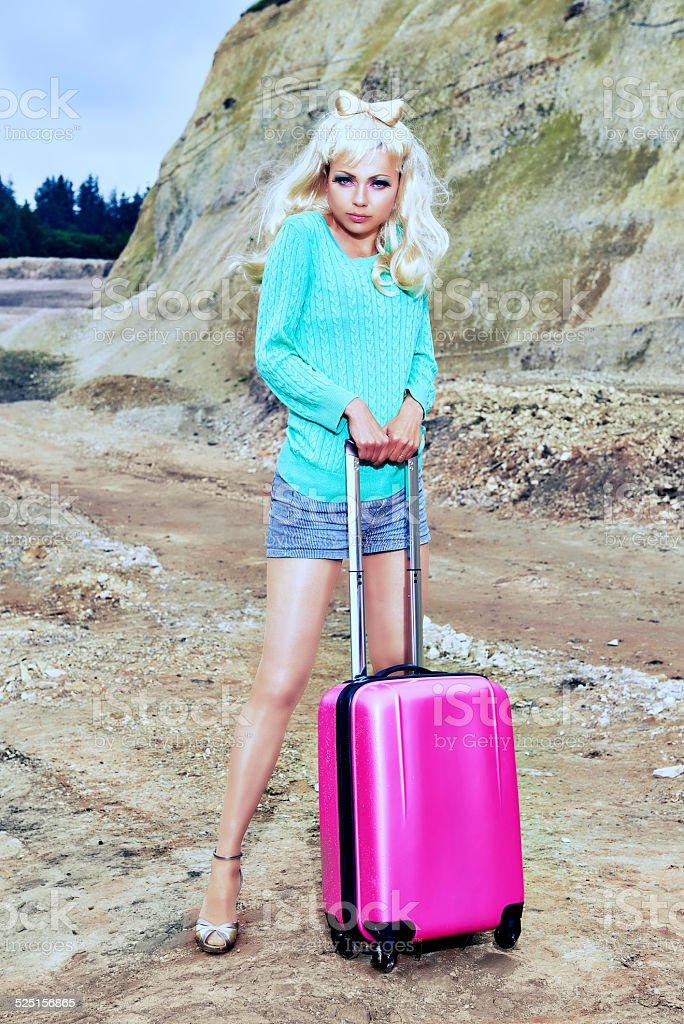 Naive cute pinup girl with pink suitcase travelling in dessert stock photo