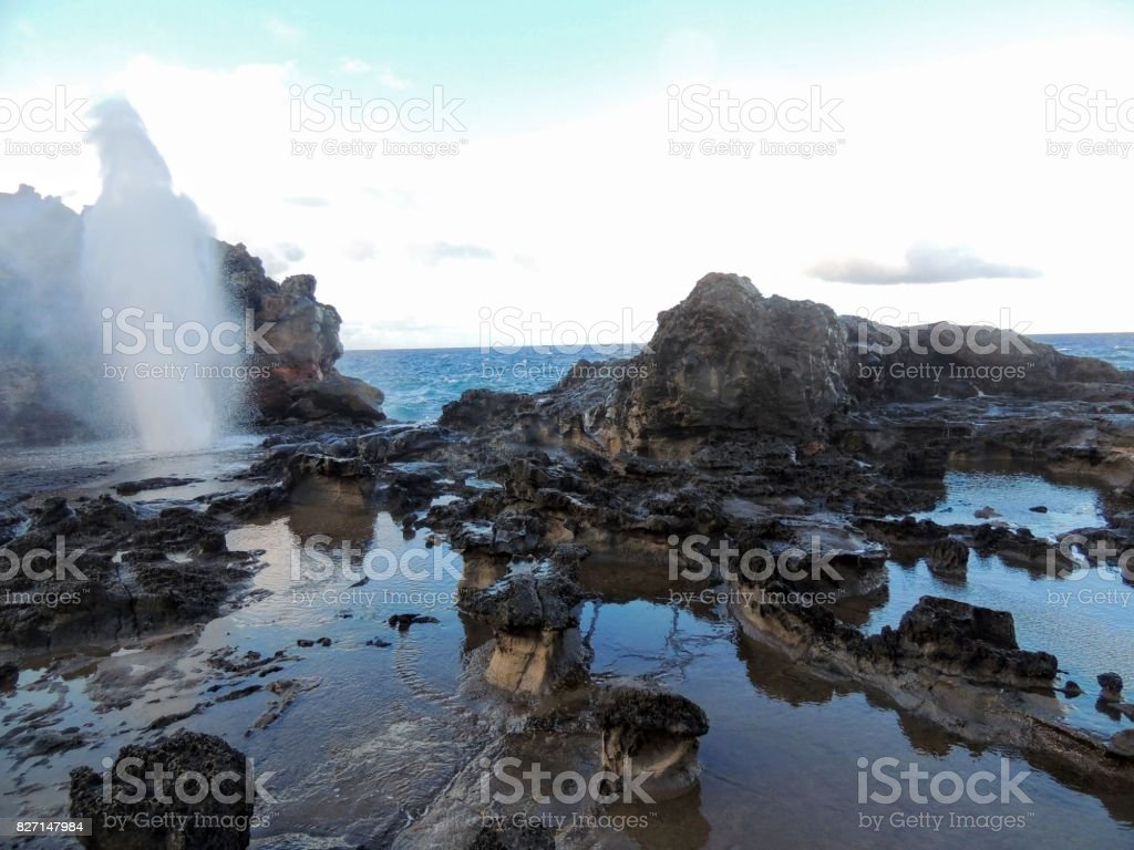 Nakalele Blowhole with water spraying out that was created from Pacific Ocean waves hitting the tall rocky cliff coastline that was created from lava on Maui, Hawaii, USA sky reflecting off the still water stock photo