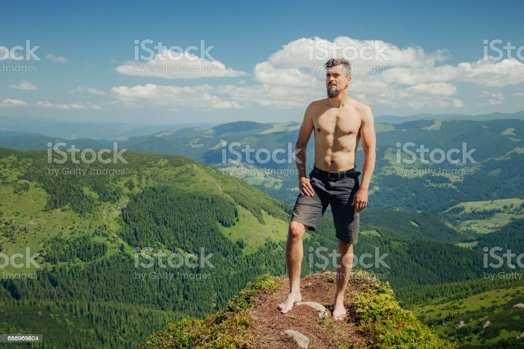 Naked athletic man standing on the mountain rock stock photo