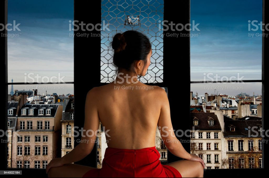 Naked back in front of a window with a view of Paris stock photo