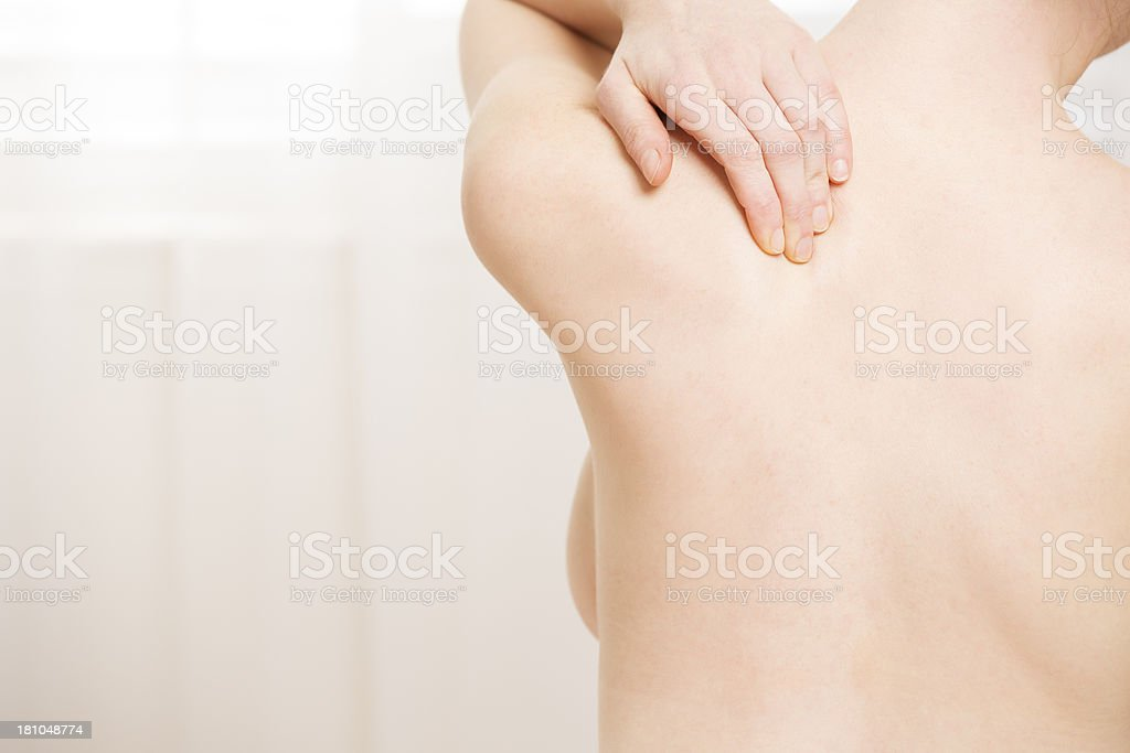 Naked back of a woman with backache from behind royalty-free stock photo