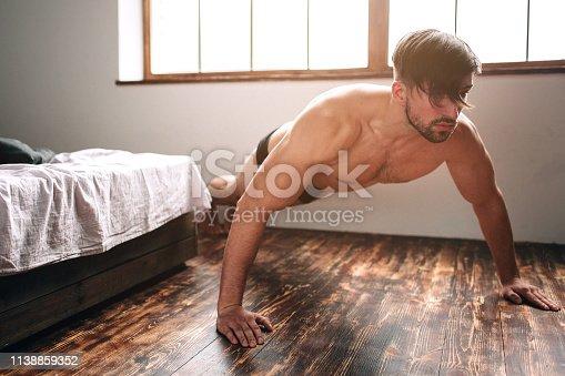 istock Naked bearded dark-hair man doing push-up exercise home morning. 1138859352