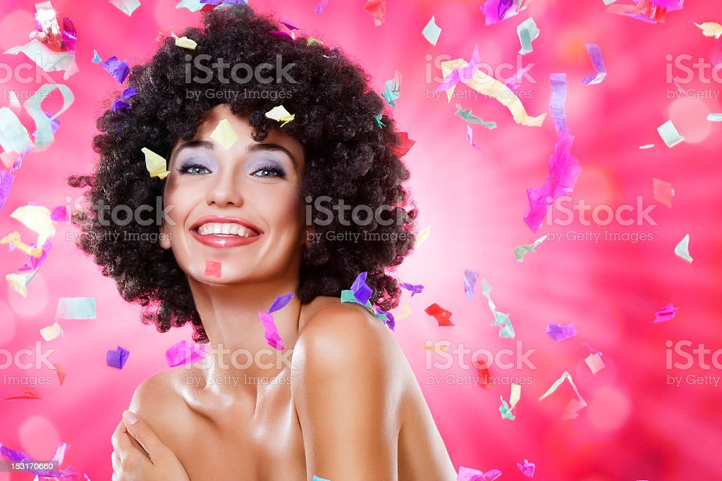 Naked Caucasian woman with an afro smiling under confetti stock photo