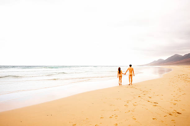 naked couple walking on the beach - naked women with animals stock photos and pictures