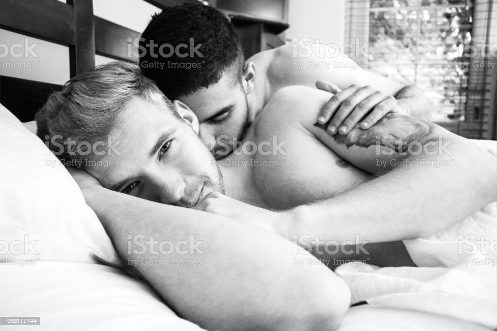 Naked, gay lovers, husbands in bed, holding and kissing stock photo